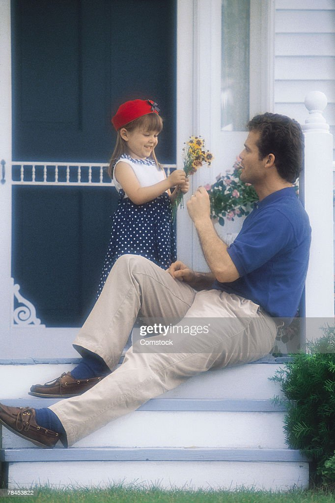 Father on porch receiving flowers from daughter : Stockfoto