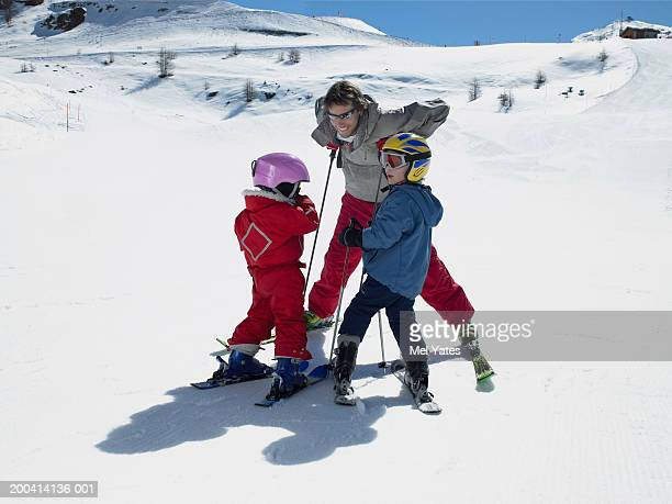 Father on skis with son and daughter (3-6) wearing helmets, smiling