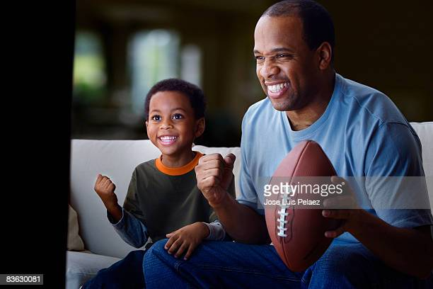 Father on son watching football game