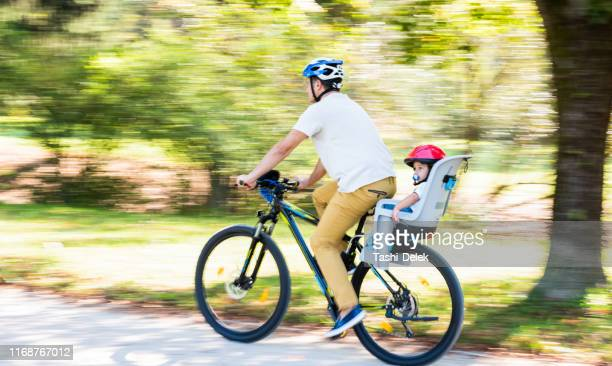 father on the bicycle with his son in the back - family with one child stock pictures, royalty-free photos & images