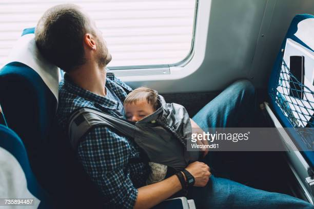 Father on the train holding his sleeping baby in a baby carrier