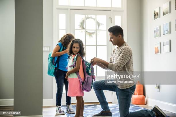 father packing daughters backpacks for school - 新学期 ストックフォトと画像