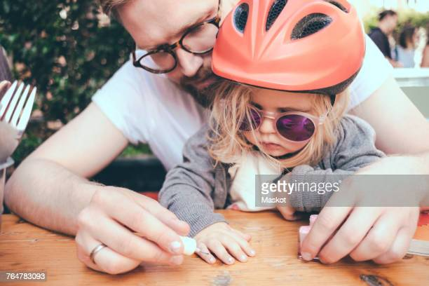 Father painting daughters nails at table outdoors