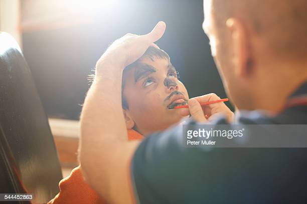 Father painting sons lips for halloween