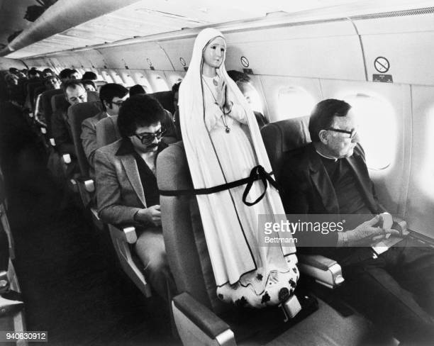 Father Patrick Moore, of the Scarborough Foreign Mission, sits next to the World Pilgrim Statue of our Lady of Fatima en route to the Port of Spain,...