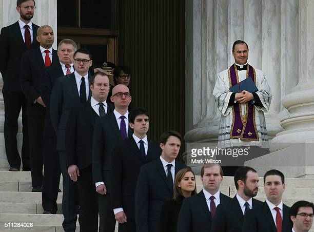 Father Paul Scalia son of Associate Justice Antonin Scalia watches as his father's casket is carried up the steps of the Supreme Court building...