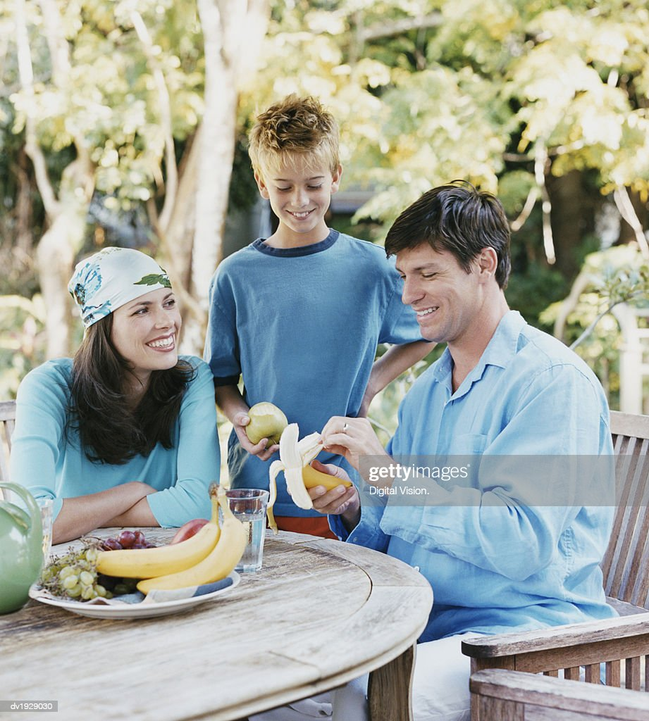 Father Peeling a Banana and Sitting at a Table in His Garden by His Son and Wife : Stock Photo
