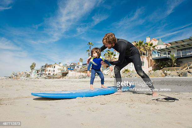 Father persuading son to go on surfboard