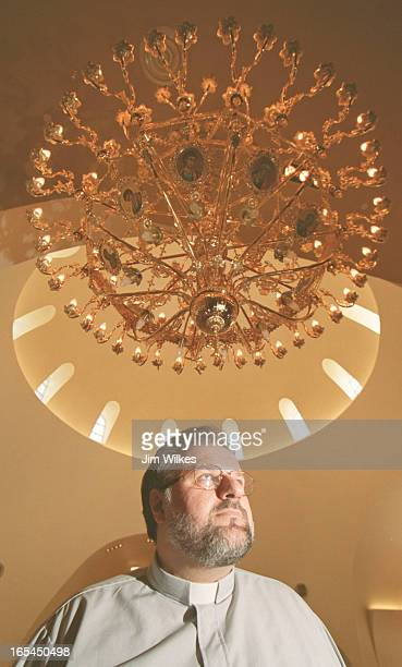 Father Peter Avgeropoulos stands under one of six golden chandeliers beneath the hoge grand dome of the resurrected Greek Orthodox Cathedral of the...