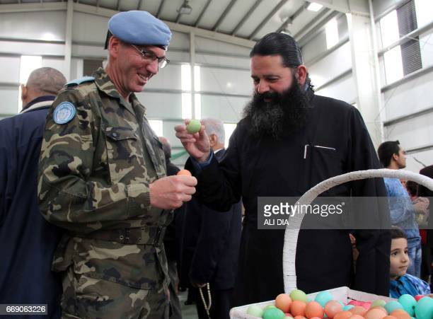 Father Philip AlAqla assistant of the new Greek Orthodox Bishop of the southern Lebanese city of Marjayoun holds an easter egg next to UNIFIL's...