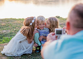father photographing his three cute child