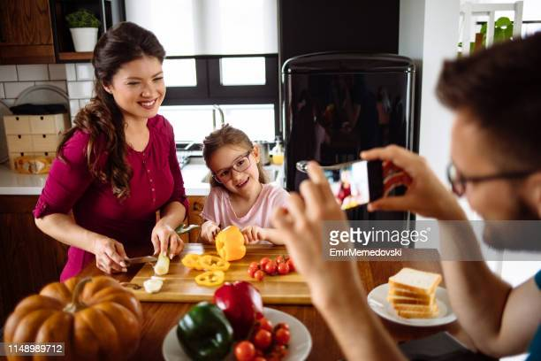 Father photographing family at table in kitchen