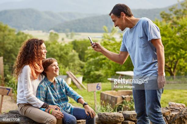 Father photographing family through smart phone