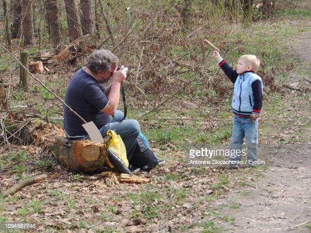 Father Photographing Son In Forest