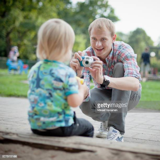 Father photographing son (1-2) in playground