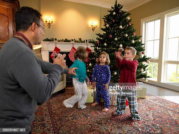 father photographing three children (3-6) beside christmas tree - stockings no shoes stock pictures, royalty-free photos & images