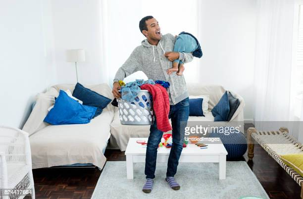 Father picking up laundry and baby