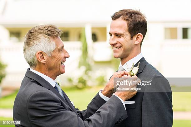 Father Pinning Boutonniere On Groom's Suit In Garden