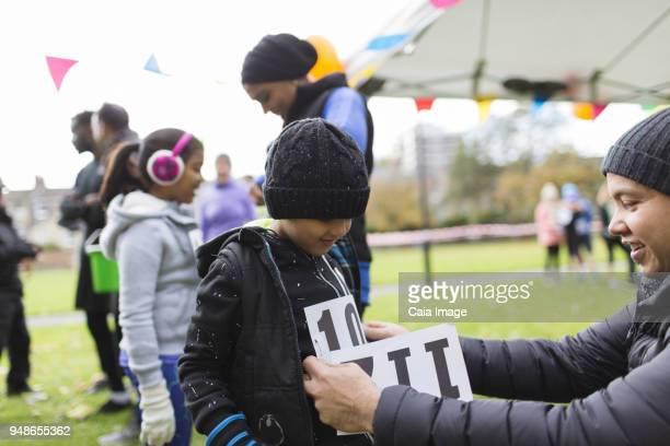 father pinning marathon bib on son at charity run in park - 40s pin up girls stockfoto's en -beelden