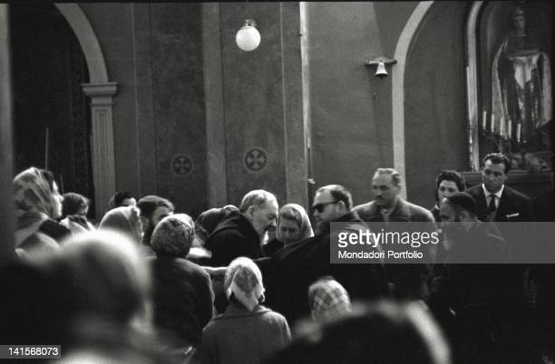 Father Pio of Pietrelcina surrounded by a crowd of parishioners at the convent of San Giovanni Rotondo Italy 1958