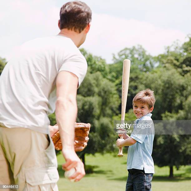father pitching baseball to son - 野球バット ストックフォトと画像