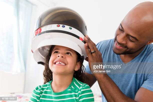 Father placing astronaut helmet on daughter
