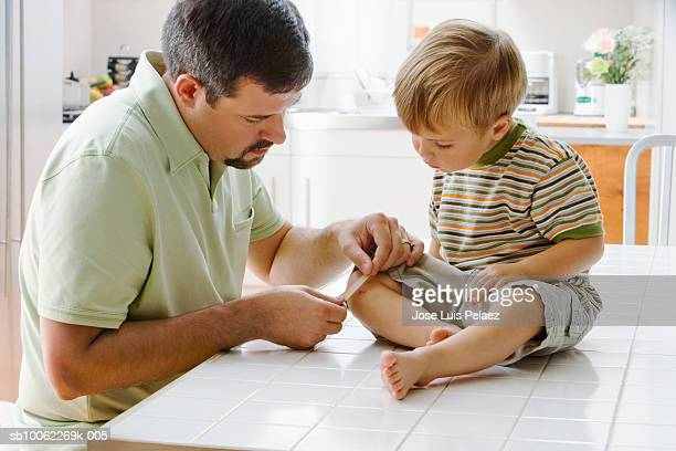 Father placing bandage on son's (3-4) knee