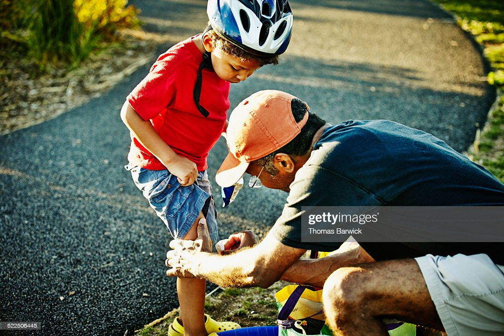 Father placing bandage on young son's knee : Stock Photo