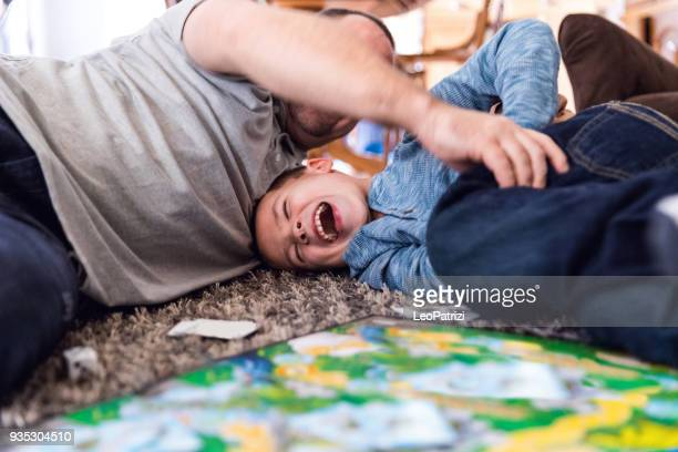father play at home with son - game board stock photos and pictures