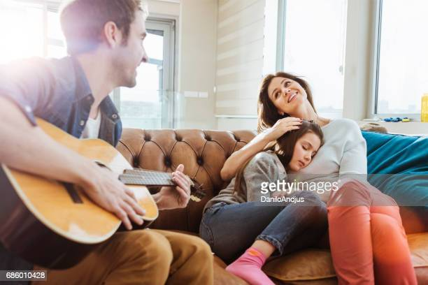 father play the guitar for his family