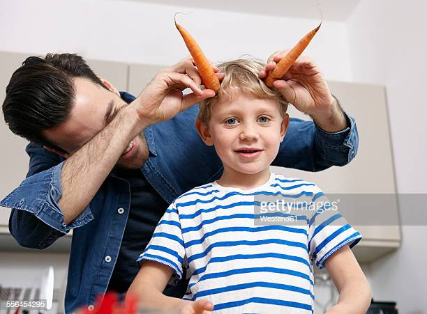 Father playin with kids in kitchen, making carrot horns
