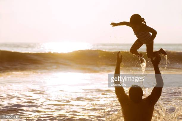 Father Playing and Throwing Daughter Up in Ocean at Sunset