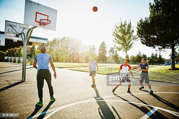 Father playing basketball with daughters