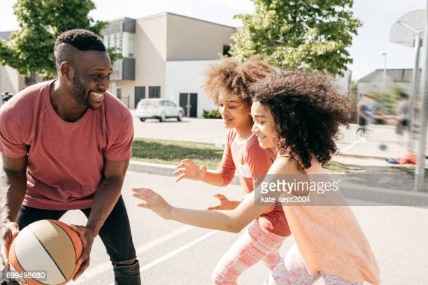 Father playing basketball with kids