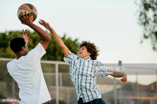 father playing basketball with son at court - blocking sports activity stock pictures, royalty-free photos & images