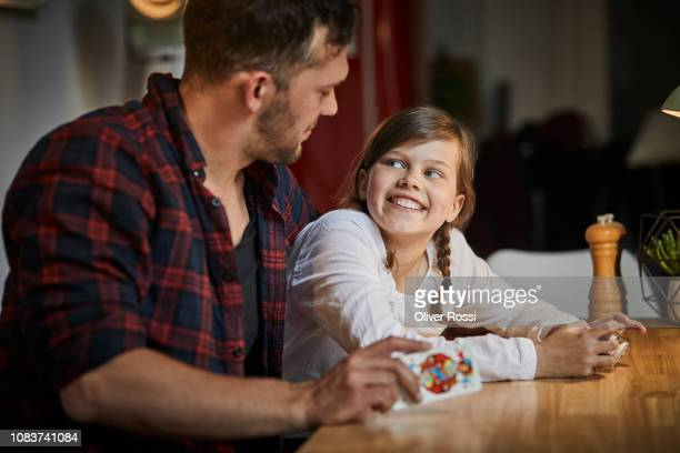 father playing cards with daughter at table at home - stubble stock pictures, royalty-free photos & images