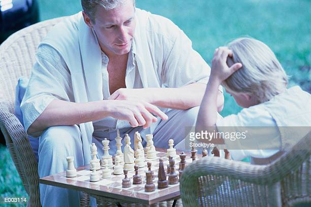 Father playing chess with child