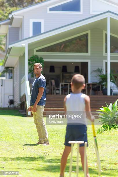 Father playing cricket with son