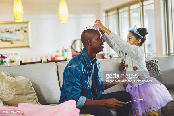 father playing dress up with his little girl at home - princess stock pictures, royalty-free photos & images