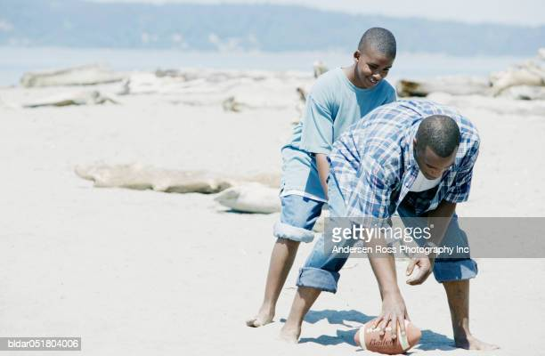 Father playing football with his son on the beach