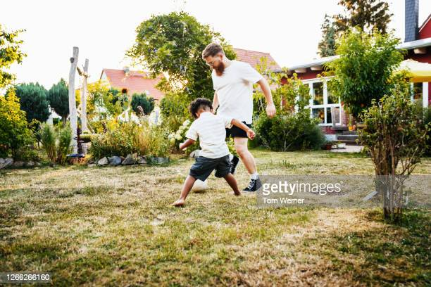 father playing football with his young young son in back garden - sports equipment stock pictures, royalty-free photos & images
