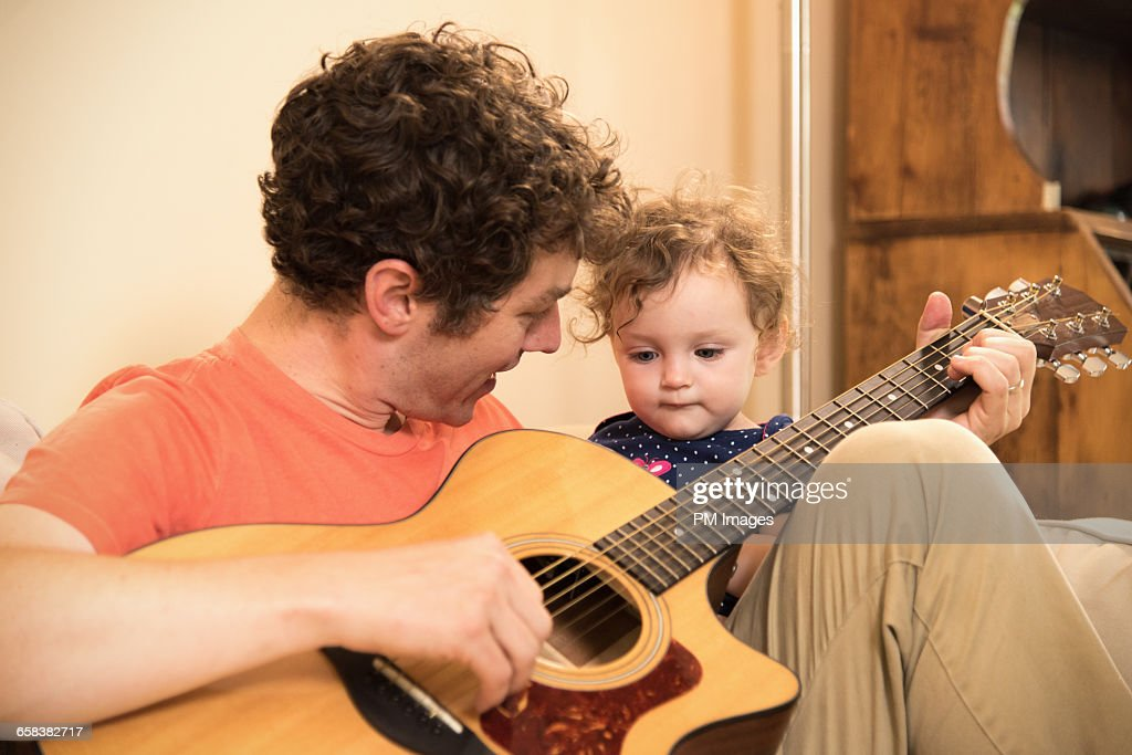 Father Playing Guitar For Baby Girl Stock Photo - Getty Images
