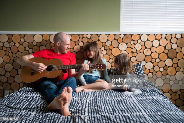 Father playing guitar for his daughters
