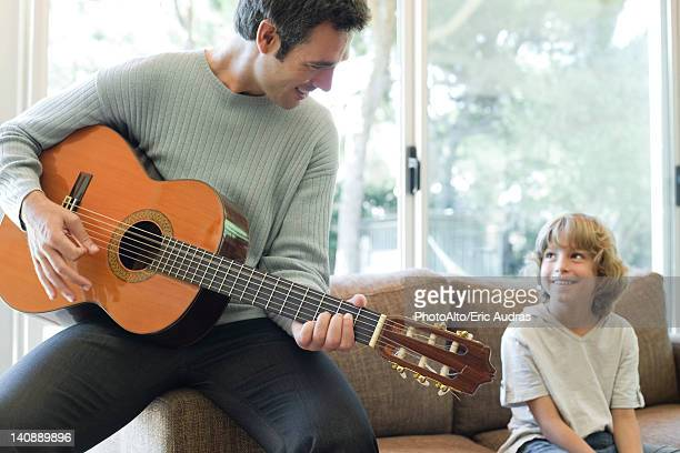 Father playing guitar for son