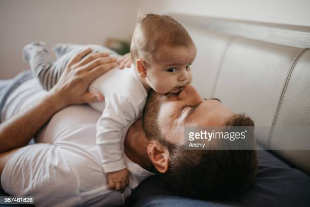 father playing in bed with his little baby boy - father stock pictures, royalty-free photos & images