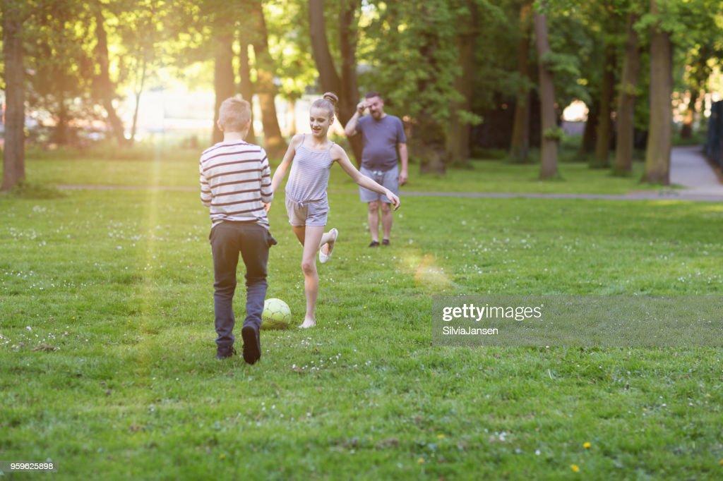 Vater spielen Fußball mit jungen und Mädchen im park : Stock-Foto