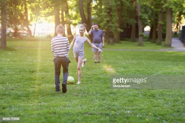 Vater spielen Fußball mit jungen und Mädchen im park