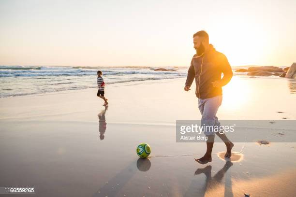 father playing soccer with his son on the beach - active lifestyle stock pictures, royalty-free photos & images