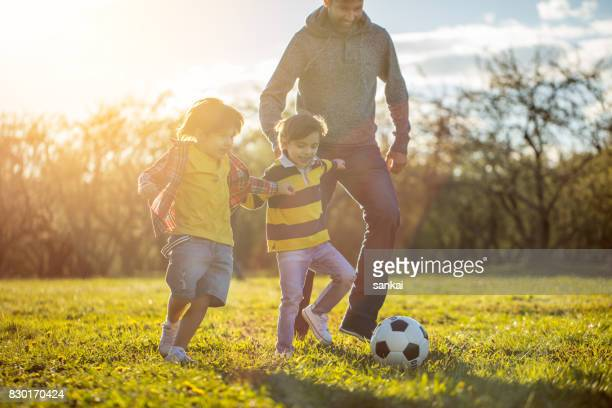 father playing soccer with two sons at the public park at sunset - in the park day 3 imagens e fotografias de stock