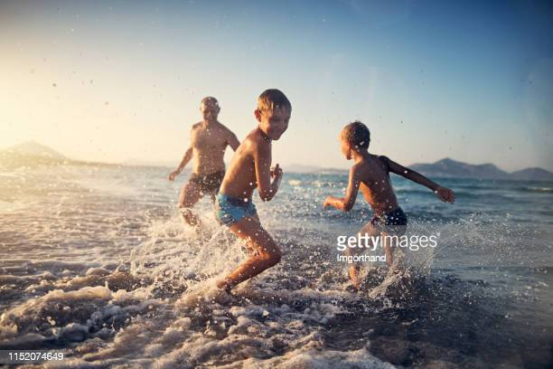 Father playing tag with kids on the beach